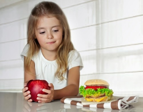 Little girl choose between apple and hamburger.Unhealthy nutrition.